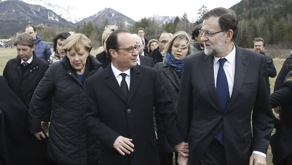 France's President Francois Hollande (C), Spain's Prime Minister Mariano Rajoy (R) and German Chancellor Angela Merkel walk on a field near the crash site of Germanwings Airbus A320 near Seyne-les-Alpes in this March 25 - Sputnik France