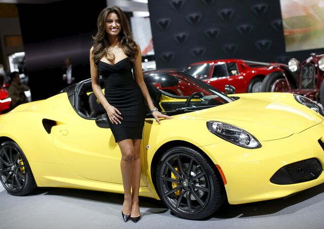 A model poses next to an Alfa Romeo sports car at the 2015 New York International Auto Show in New York City, April 1, 2015