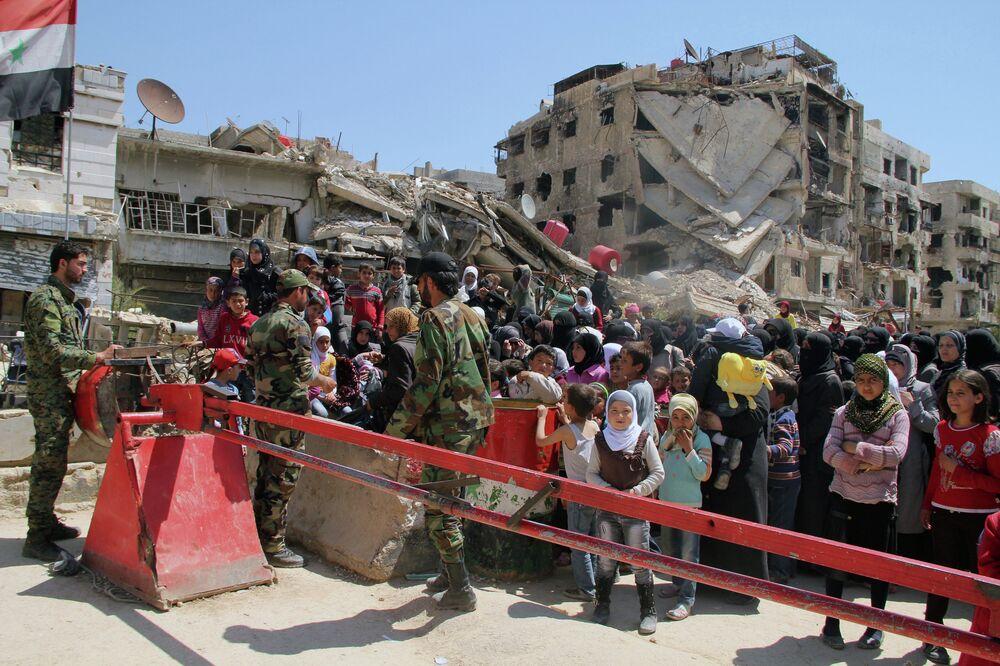Les femmes et les enfants quittent le camp de Yarmouk situé au sud de Damas
