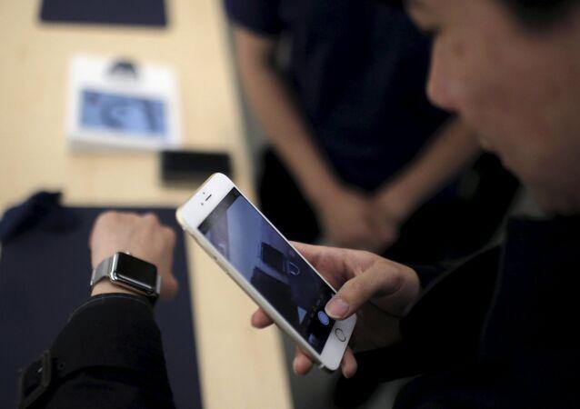 Un client prend une photo d'une montre Apple avec son téléphone portable après dans un Apple Store au centre-ville de Shanghai, le 10 avril 2015
