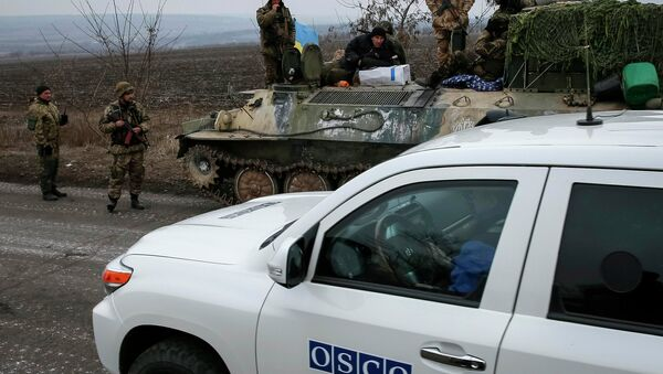 A vehicle of Special Monitoring Mission of the Organization for Security and Cooperation (OSCE) to Ukraine rides along a convoy of Ukrainian armed forces in Paraskoviyvka, eastern Ukraine, February 26, 2015. - Sputnik France