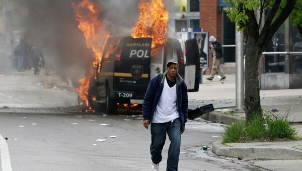 A man walks past a burning police vehicle, Monday, April 27, 2015, during unrest following the funeral of Freddie Gray in Baltimore. Gray died from spinal injuries about a week after he was arrested and transported in a Baltimore Police Department van. - Sputnik France