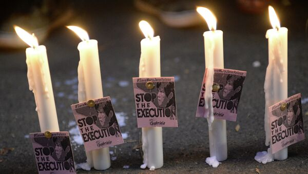 Candles and portraits of Filipina Mary Jane Veloso, who is due for execution in Indonesia, are seen during the vigil in front of the Indonesian embassy in Manila on April 27, 2015. - Sputnik France