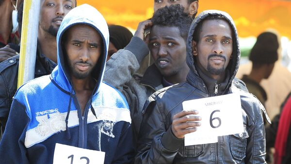 Migrants hold their numbers after disembarking from the Italian Navy ship Chimera in the southern harbour of Salerno - Sputnik France