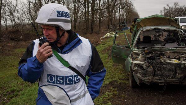 OSCE observers inspect a damaged car near Shyrokyne village, eastern Ukraine, Monday, March 30, 2015 - Sputnik France