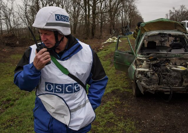 OSCE observers inspect a damaged car near Shyrokyne village, eastern Ukraine, Monday, March 30, 2015