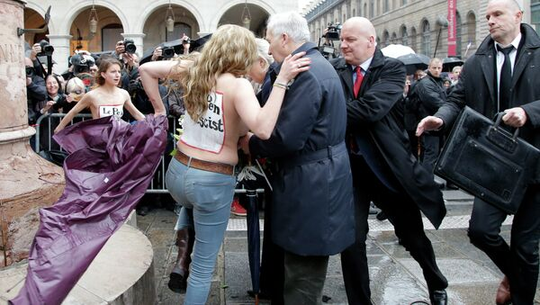 Femen activists with Le Pen Top Fascist painted on their bodies appear as France's far-right National Front president Marine Le Pen places a wreath at Joan of Arc statue during its annual May Day march, in Paris, France, Friday, May 1, 2015 - Sputnik France