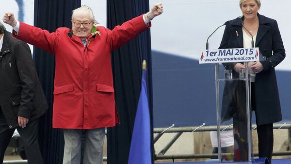 France's far-right National Front political party leader Marine Le Pen (R) watches as her father Jean-Marie Le Pen, party founder and honorary president, reacts on the podium at their traditional May Day tribute to Joan of Arc in Paris, France, May 1, 2015 - Sputnik France