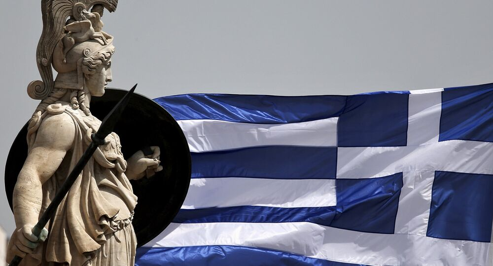 A Greek national flag flutters next to a statue of ancient Greek goddess Athena, in Athens May 21, 2015