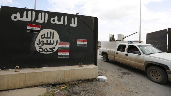 Iraqi security forces ride a vehicle past a wall painted with the black flag commonly used by Islamic State militants, near former Iraqi president Saddam Hussein's palace in Tikrit April 1, 2015 - Sputnik France