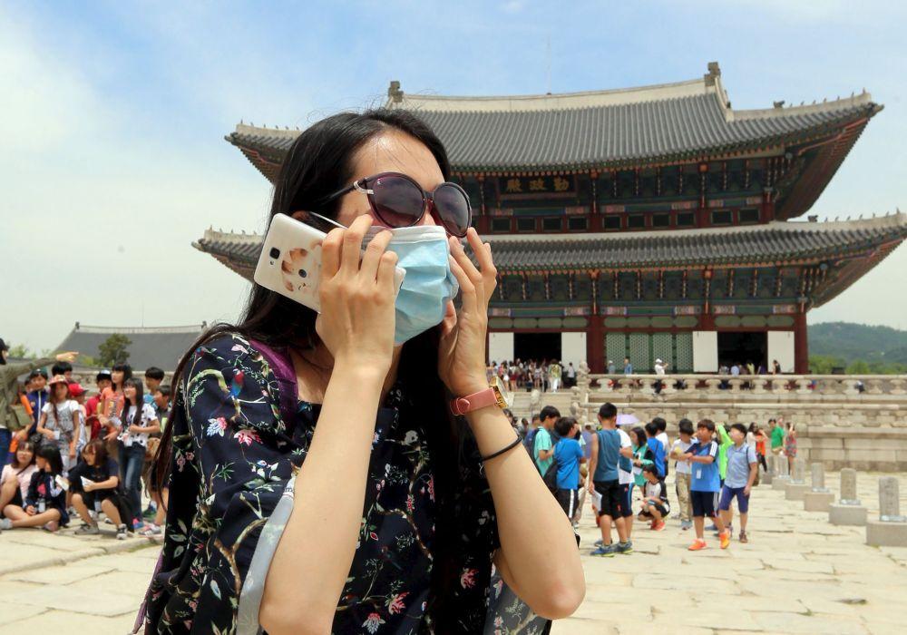 Une touriste chinoise portant un masque lors d'une visite au palais royal de Gyeongbok à Séoul