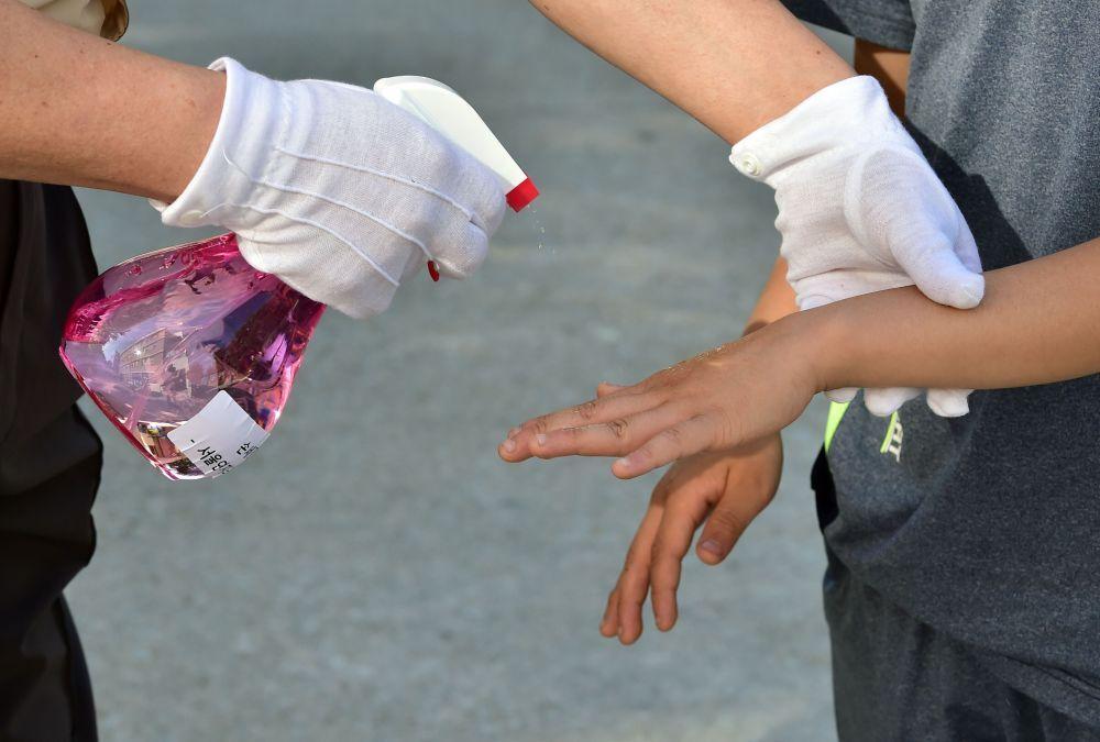Un employé d'une école primaire de Séoul désinfecte les mains des élèves