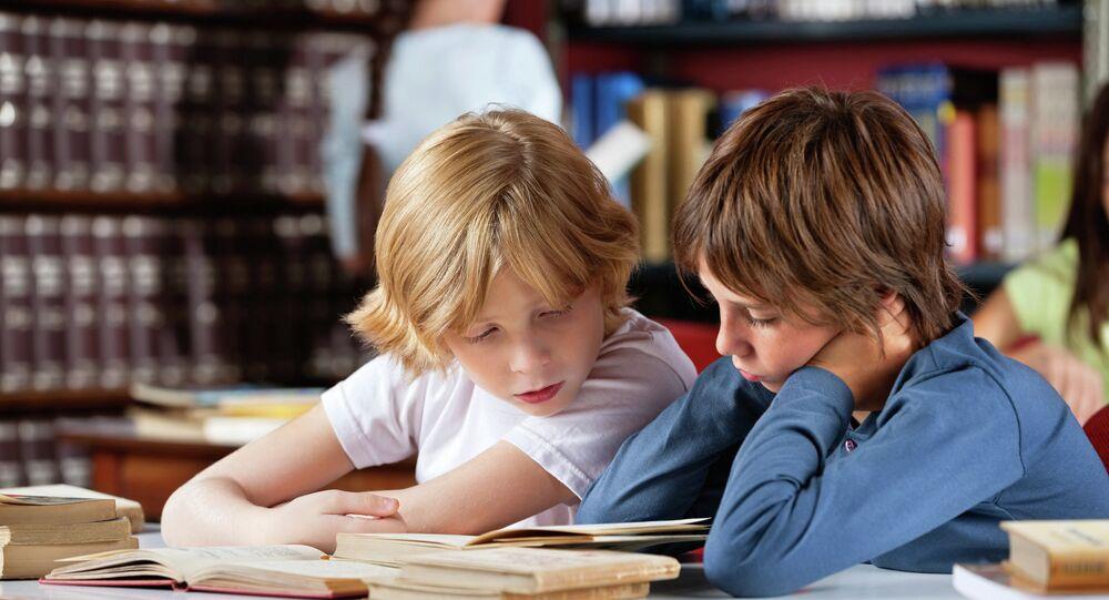 Les écoliers lisent les livres dans une bibliothèque