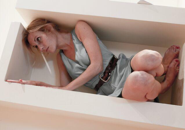 Une femme placée dans une boîte