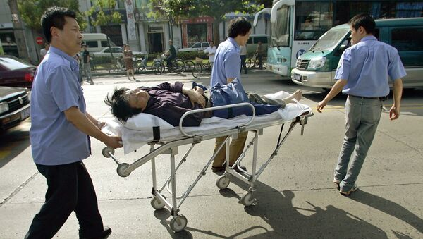 Medical rescuers transport a wounded motorbike rider on a stretcher after a traffic accident in Shanghai, 06 June 2005. - Sputnik France
