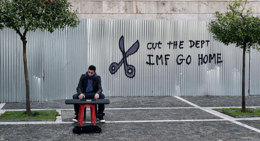 Un musicien jouant dans une rue d'Athènes près d'un panneau stigmatisant le FMI
