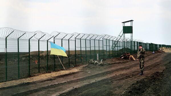 A Ukrainian border guard officer speaks on a phone near a national flag attached to the fence on the Ukrainian-Russian border near Hoptivka, Kharkiv region, eastern Ukraine - Sputnik France