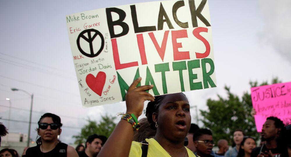 Une habitante de Miami, tient une pancarte Black Lives Matter, avec les nomes de Michael Brown et Eric Garner, deux hommes noirs tués par la police