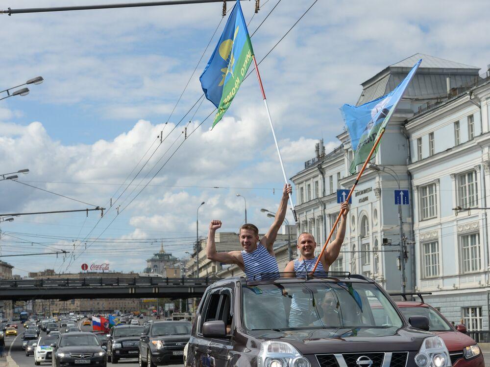 Des parachutistes en fête roulent en voiture dans une rue de Moscou