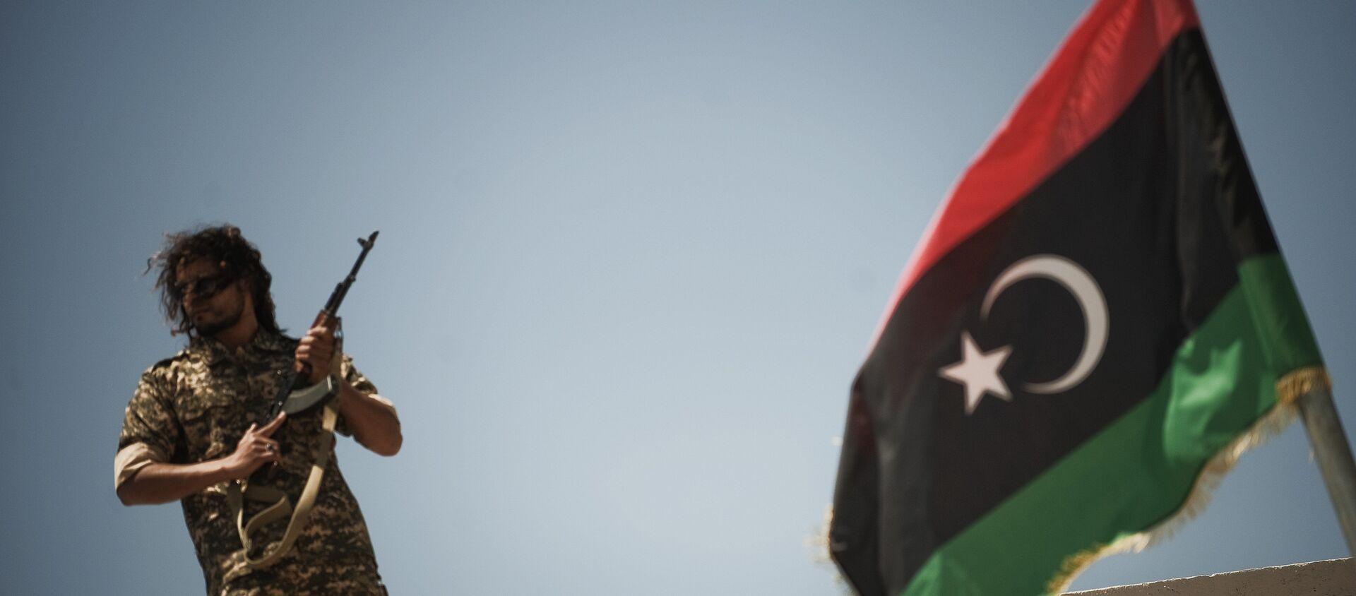 Un membre des forces de sécurité libyennes se tient sur un toit alors que le ministre libyen de la justice par intérim, Ali Hamiada, visite la nouvelle prison d'Al-Hadba et le tribunal spécial le 26 mai 2012 à Tripoli. La prison, qui peut accueillir 100 prisonniers politiques de haut rang, accueillera les procès des personnalités pro-mamer Kadhafi - Sputnik France, 1920, 23.12.2020