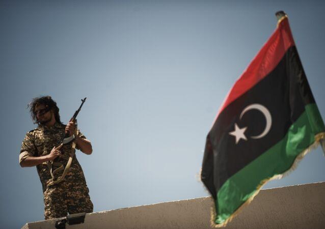 Un membre des forces de sécurité libyennes se tient sur un toit alors que le ministre libyen de la justice par intérim, Ali Hamiada, visite la nouvelle prison d'Al-Hadba et le tribunal spécial le 26 mai 2012 à Tripoli. La prison, qui peut accueillir 100 prisonniers politiques de haut rang, accueillera les procès des personnalités pro-mamer Kadhafi