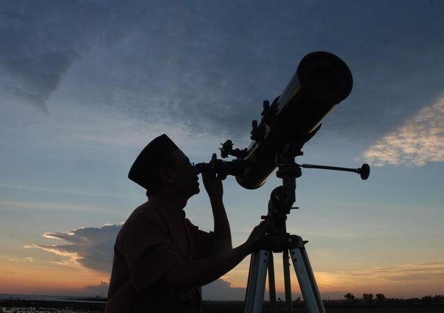 un homme regarde la Lune à travers un télescope, image d'illustration