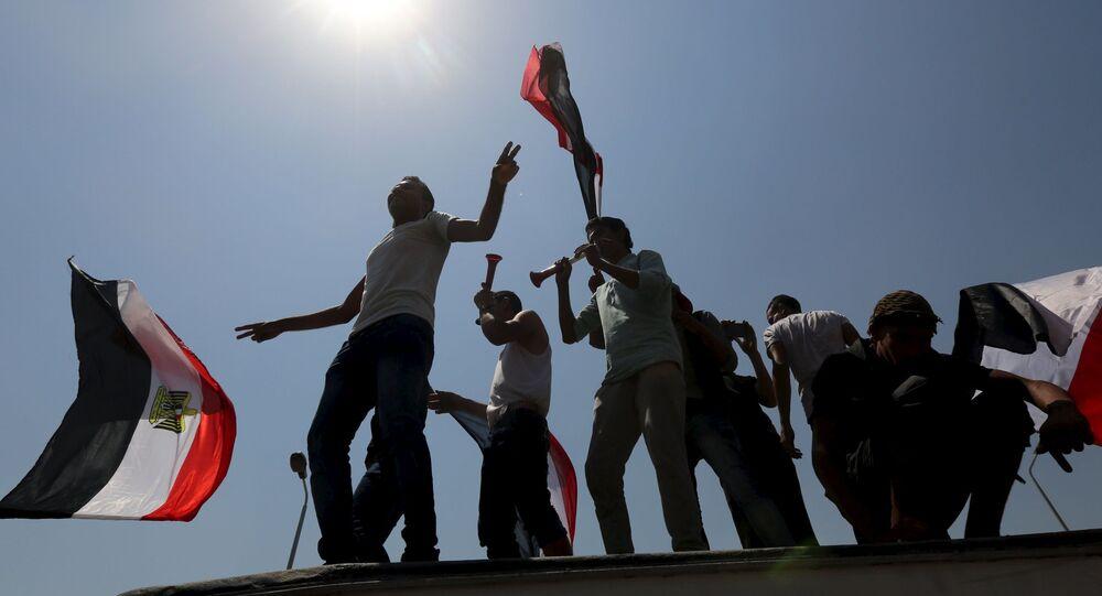 Les gens applaudissent en portant les drapeaux nationaux alors qu'ils se rassemblent sur la place Tahrir pour célébrer l'extension du canal de Suez, au Caire, en Égypte, le 6 août 2015. L'Égypte inaugurera jeudi en grande pompe le prolongement du canal de Suez, pièce maîtresse des plans du président Abdel Fattah al-Sisi pour revitaliser l'économie du pays après des années de troubles politiques préjudiciables.