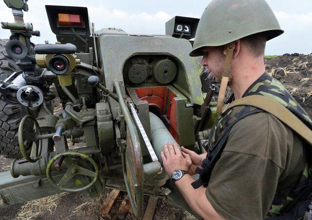 Un soldat ukrainien charge un canon