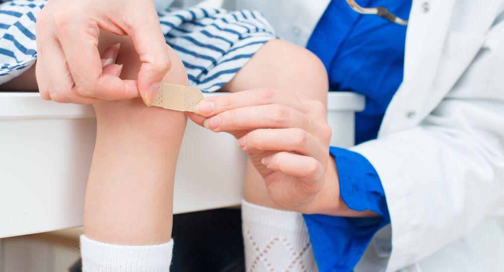 Docteur met un pansement sur le genou d'enfant