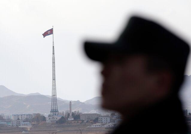 Un soldat sud-coréen avec un drapeau nord-coréen flottant derrière lui