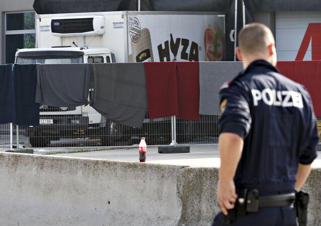 Un officier de police examine le camion où des corps de 71 migrants ont été trouvés jeudi 27 août 2015, Autriche