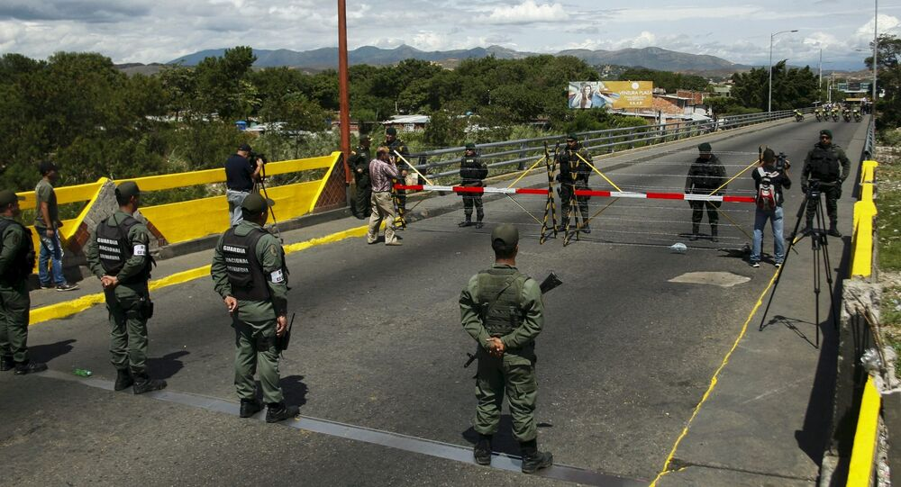 Les militaires vénézuéliens (en bas) faisant face aux soldats colombiens à la frontière commune