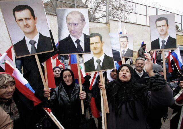 Des manifestants syriens avec des portraits de Vladimir Poutine et de Bachar el-Assad à Damas