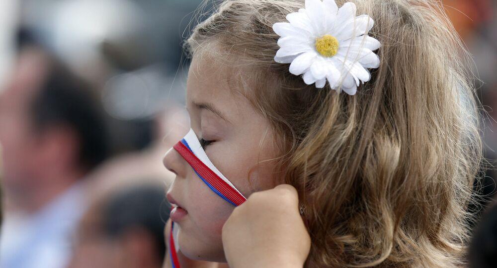 Une fille avec le ruban de couleurs du drapeau russe