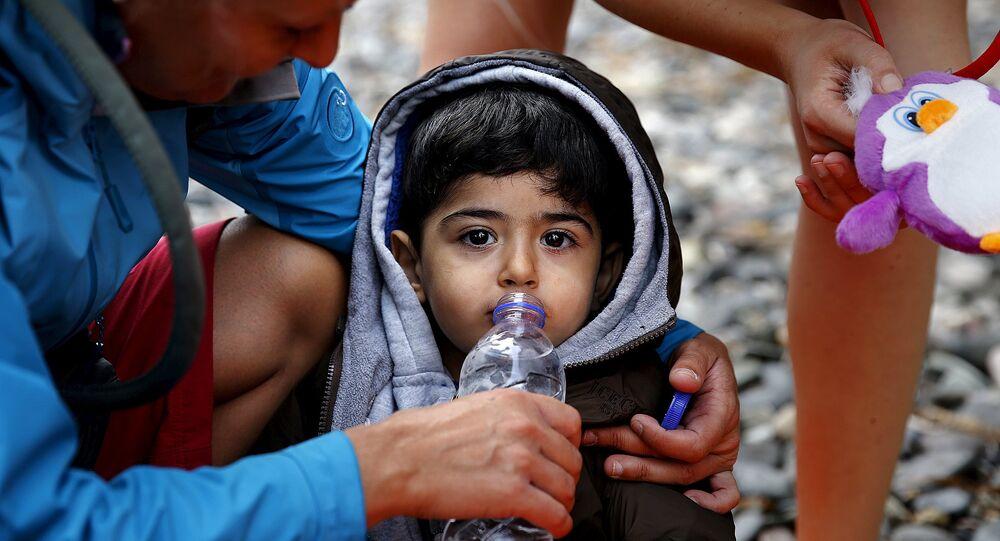 Une volontaire donne à boire à un petit réfugié syrien