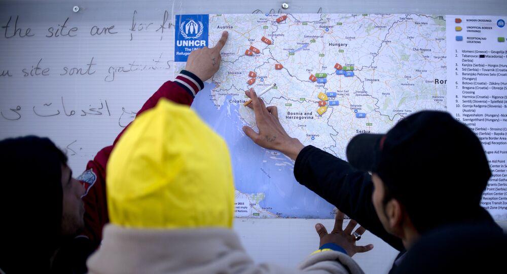 Des migrants examinent une carte des Balkans de l'Ouest, Oct. 27, 2015.