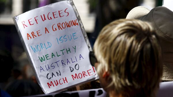 Protesters hold placards at the 'Stand up for Refugees' rally held in central Sydney. Australia is negotiating a deal with the Philippines to transfer asylum seekers being held indefinitely in controversial detention centres on remote, impoverished islands, Australia's immigration minister said on October 9, 2015 - Sputnik France