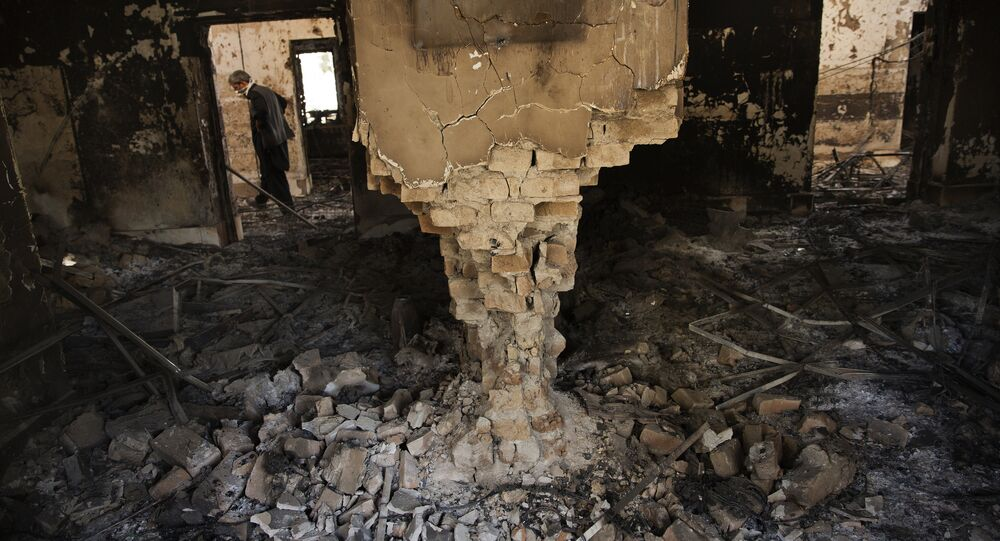A man wearing a surgical mask walks, 14 October 2015, amongst the debris of the damaged and burnt-out MSF Trauma Centre in Kunduz, northern Afghanistan