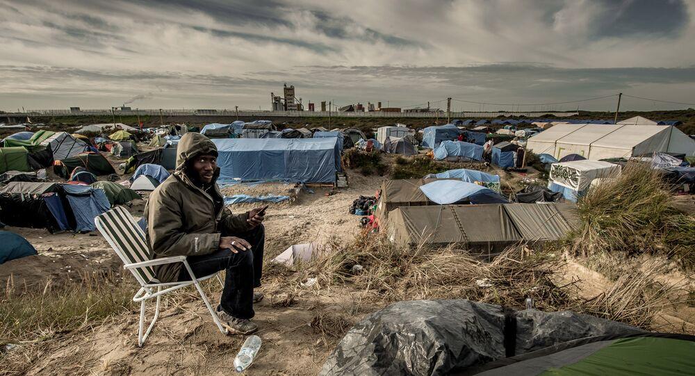 Un homme soudanais appels sa famille au Soudan, le Jungle migrants camp, Calais
