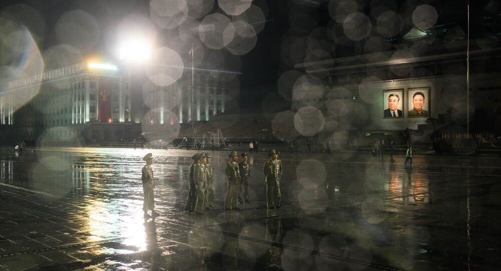 Soldats nord-coréens devant des portraits de dirigeants fin Kim Jong-un et Kim Il-sung