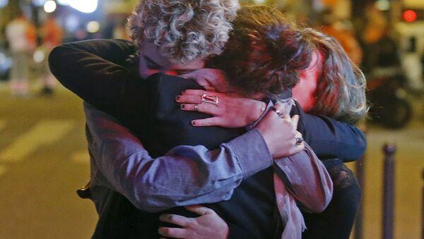 People hug on the street near the Bataclan concert hall following fatal attacks in Paris, France, November 14, 2015 - Sputnik France