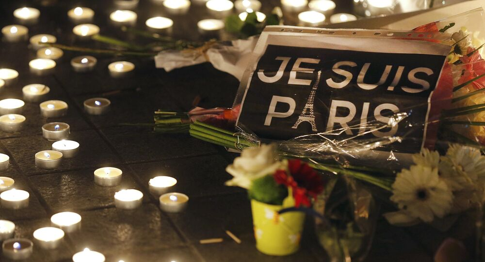 Flowers and candles are placed near the scene of a shootin the day after a series of deadly attacks in Paris , November 14, 2015