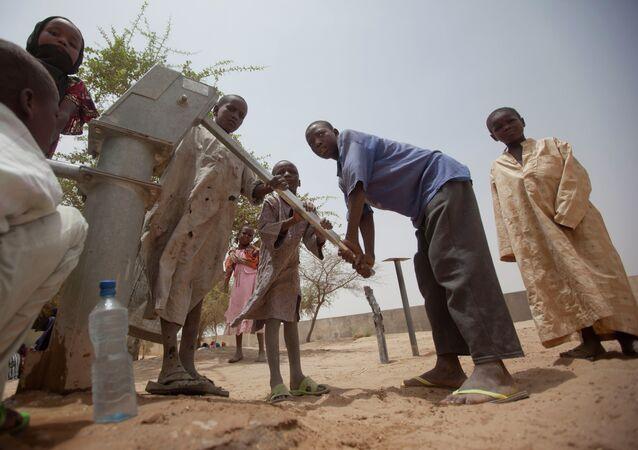 Des enfants réunis près d'un puits dans un village tchadien, dans le Sahel