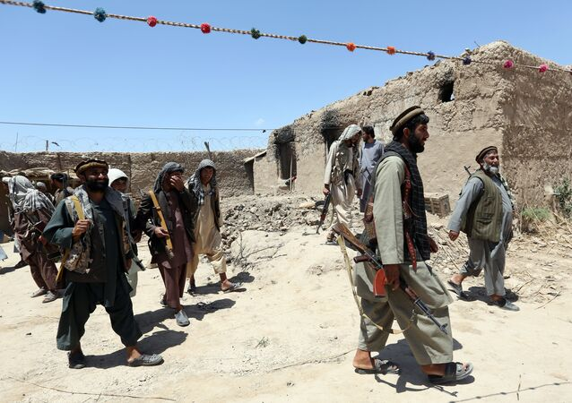 Sur cette photo de fichier du jeudi 21 mai 2015, des combattants d'une milice locale passent devant un bâtiment incendié par des combattants talibans dans le village de Talawka, dans la province de Kunduz, au nord de Kaboul, en Afghanistan.