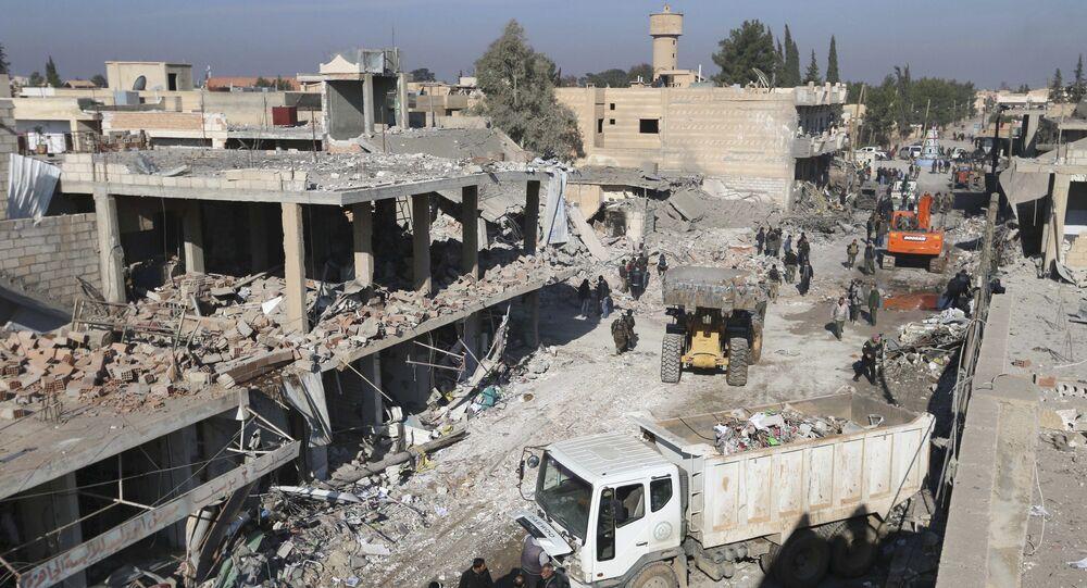 Les résidents inspectent les dommages sur un site touché par l'un des trois camions explosifs dans la ville syrienne de Tel Tamer