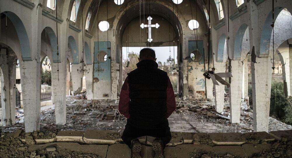 Un chrétien syrien prie dans l'église de Saint-Georges, détruite par l'EI (Daech)