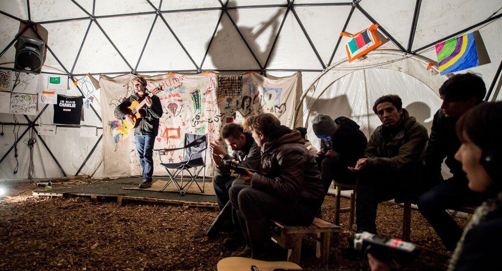 migrants écoutent un guitariste dans un théâtre improvisée, Calais