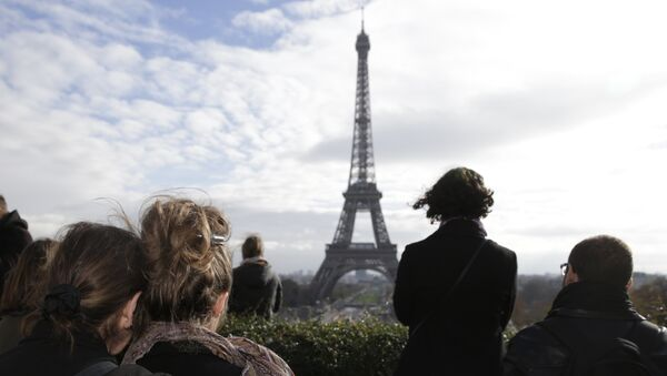 People observe in front of the Eiffel tower a minute of silence at the Place de Trocadero in Paris on November 16, 2015 to pay tribute to victims of the attacks claimed by Islamic State which killed at least 129 people and left more than 350 injured on November 13. - Sputnik France