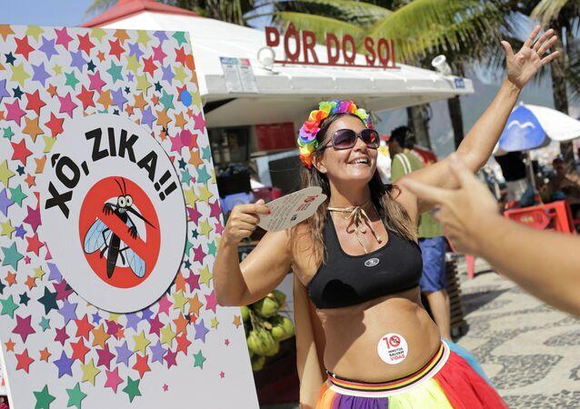 Viviane Oliveira, qui est enceinte de trois mois, danse à côté d'une pancarte en portugais: Sortez Zika lors d'un carnaval de rue sur la plage d'Ipanema à Rio de Janeiro, au Brésil, le dimanche 31 janvier 2016