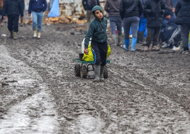 A young migrant pulls a trolley in a muddy field at a camp of makeshift shelters for migrants and asylum-seekers from Iraq, Kurdistan, Iran and Syria, called the Grande Synthe jungle, near Calais, France, February 3, 2016